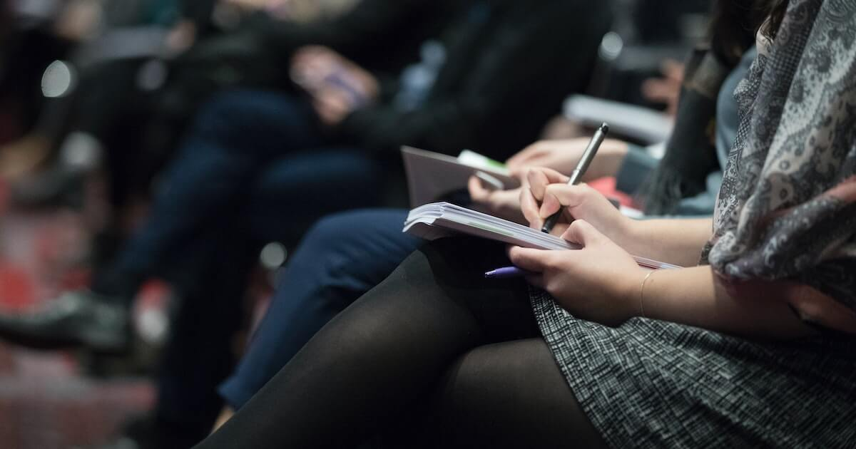 Woman sitting at a conference taking notes