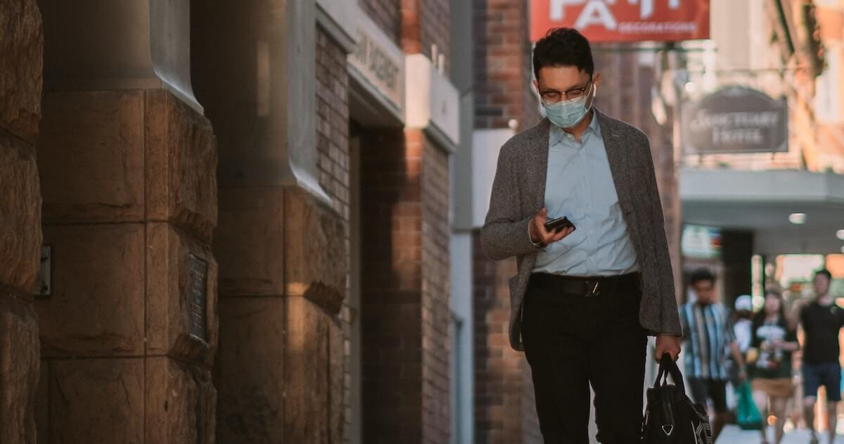 Man walking down the street wearing a face mask, looking at mobile phone