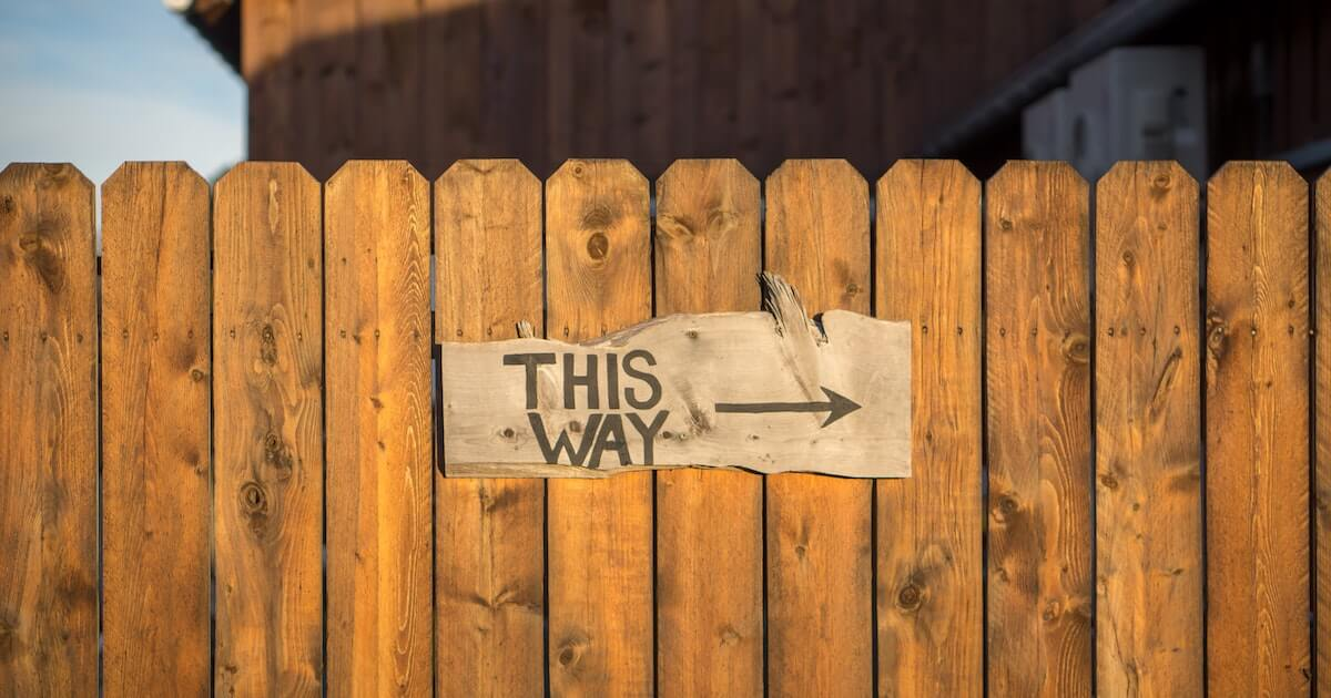 This Way sign on a fence with arrow pointing right
